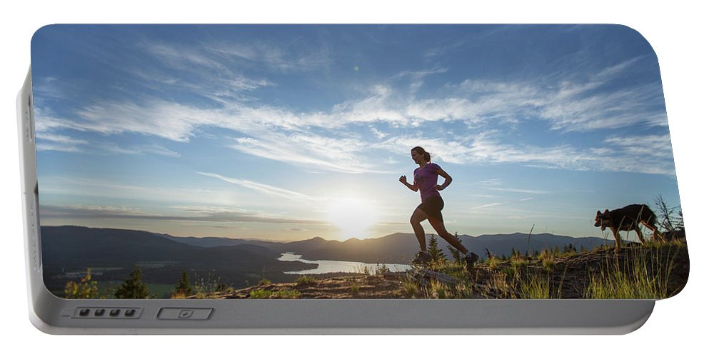 Healthy Lifestyle Portable Battery Charger featuring the photograph An Adult Woman With A Dog Running by Woods Wheatcroft