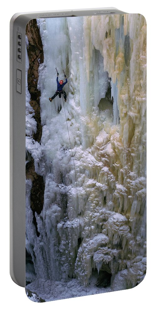 Adventure Portable Battery Charger featuring the photograph An Ice Climber Ascends A Frozen by Randy Barnes