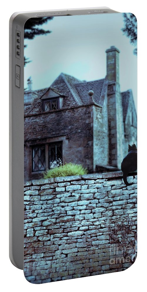 Wall Portable Battery Charger featuring the photograph Black Cat On A Stone Wall By House by Jill Battaglia