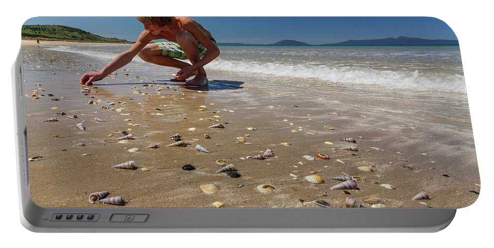 Millenial Portable Battery Charger featuring the photograph Boy Picking Seashells On The East Coast by Johnathan Ampersand Esper