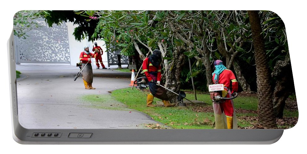 Men Portable Battery Charger featuring the photograph Camouflaged Leaf Blowers Working In Singapore Park by Imran Ahmed