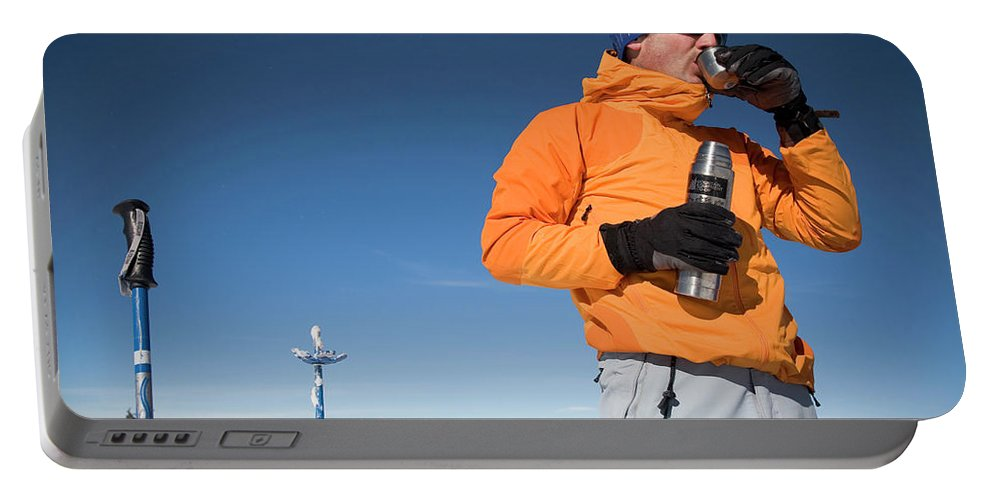 Backcountry Portable Battery Charger featuring the photograph Dressed In Orange, A Skier Sips A Warm by Michael Hanson