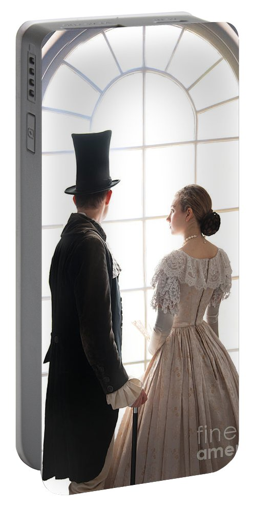Regency Portable Battery Charger featuring the photograph Historical Couple Standing In An Arched Window by Lee Avison