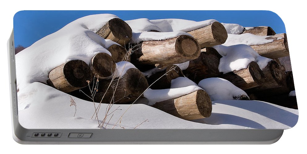 Log Portable Battery Charger featuring the photograph Log Pile In A Snow Drift In Winter by Louise Heusinkveld