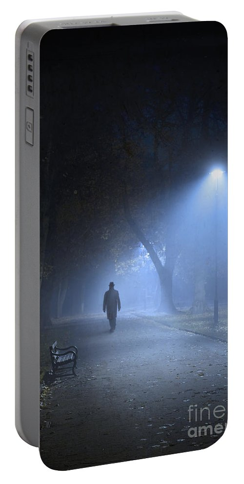 Avenue Portable Battery Charger featuring the photograph Man In Hat And Overcoat Walking In Fog On A Tree Lined Avenue In by Lee Avison