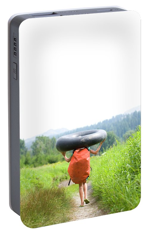 Anticipation Portable Battery Charger featuring the photograph Pre Teen Girl Carrying An Inner Tube by Woods Wheatcroft