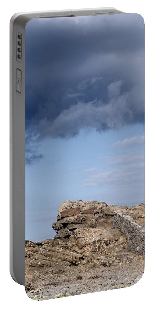 Ancient Portable Battery Charger featuring the photograph Cala Mesquida Stone Wall Against Rocks With A Stormy Sky Above - Putting Walls To Heaven by Pedro Cardona Llambias