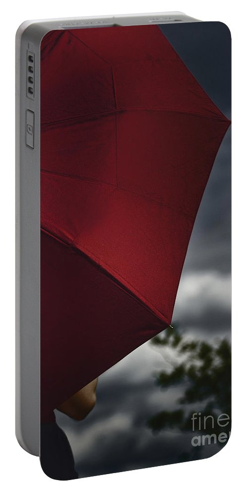 Caucasian; Woman; Female; Lady; Bright; Color; Red; Umbrella; Back; Holding; Outside; Outdoors; Storm; Stormy; Clouds; Sky; Dark; Ominous; Foreboding; Tree; Cropped; Summer; Spring; Covered; Protection Portable Battery Charger featuring the photograph Stormy by Margie Hurwich