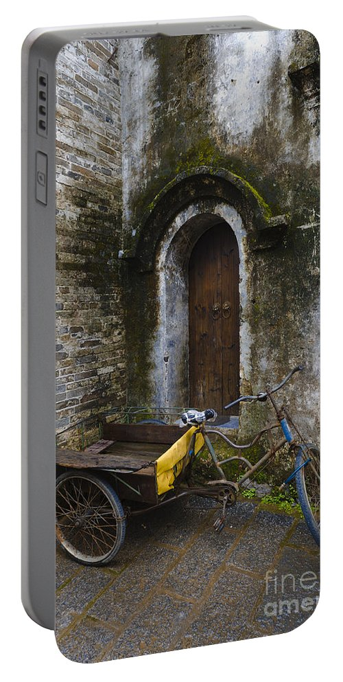 Tricycle Portable Battery Charger featuring the photograph Tricycle Parked In Alleyway by John Shaw