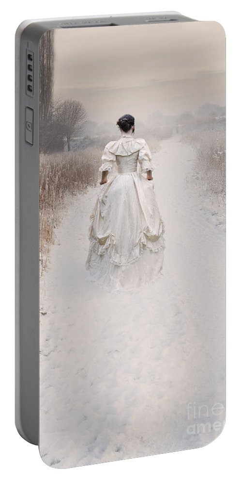 Woman Portable Battery Charger featuring the photograph Victorian Woman Walking Through A Winter Meadow by Lee Avison