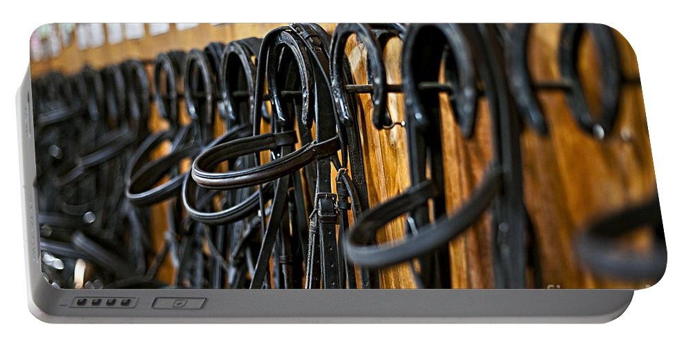 Bridles Portable Battery Charger featuring the photograph Horse Bridles Hanging In Stable by Elena Elisseeva