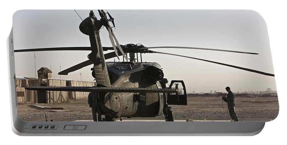 Aviation Portable Battery Charger featuring the photograph A Uh-60 Black Hawk Helicopter Parked by Terry Moore