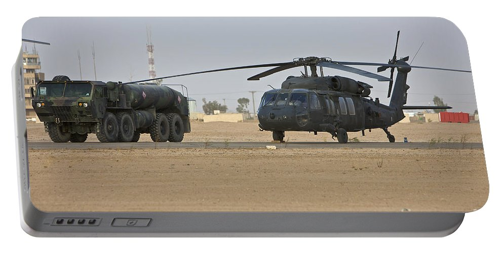 Aviation Portable Battery Charger featuring the photograph A Uh-60 Black Hawk Helicopter by Terry Moore