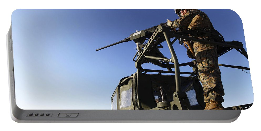 Camouflage Clothing Portable Battery Charger featuring the photograph A Machine Gunner Mounts A M-2 by Stocktrek Images
