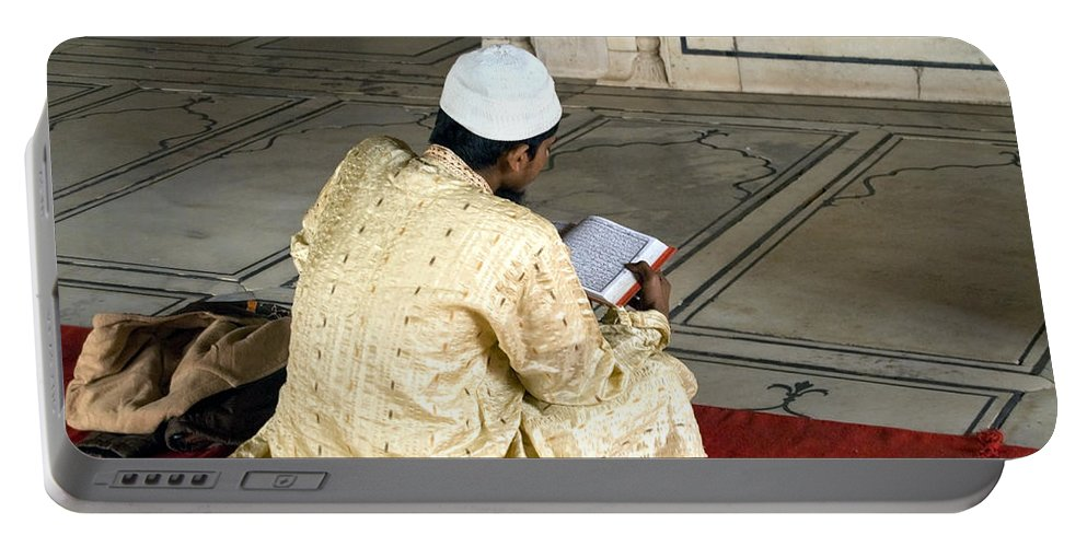 Quran Portable Battery Charger featuring the photograph A Pious Devotee Reading The Quran Inside The Jama Masjid In Delhi by Ashish Agarwal