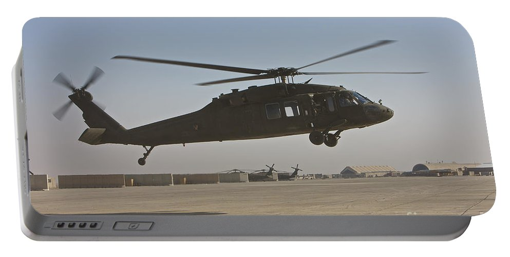 Aviation Portable Battery Charger featuring the photograph A Uh-60 Black Hawk Landing by Terry Moore