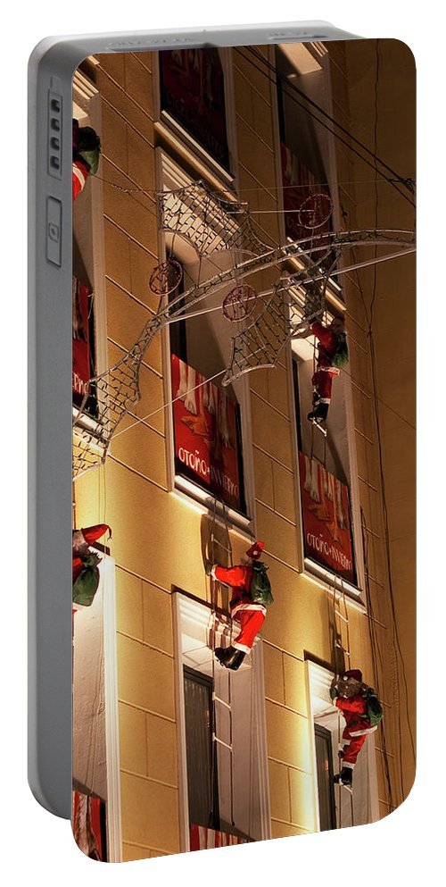 Madrid Portable Battery Charger featuring the photograph A Wall Of Sneaky Santas by Lorraine Devon Wilke