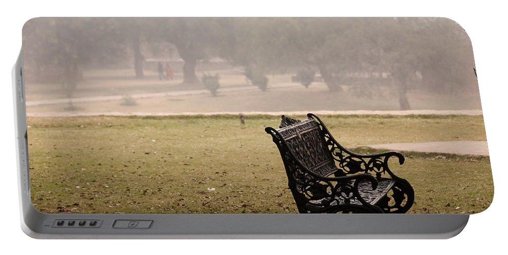 Bench Portable Battery Charger featuring the photograph A Wrought Iron Black Metal Bench Under A Tree In The Qutub Minar Compound by Ashish Agarwal