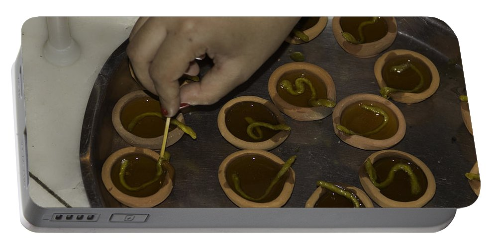 Action Portable Battery Charger featuring the photograph Adjusting The Wicks In A Plate Full Of Oil Lamps As Part Of Diwali by Ashish Agarwal