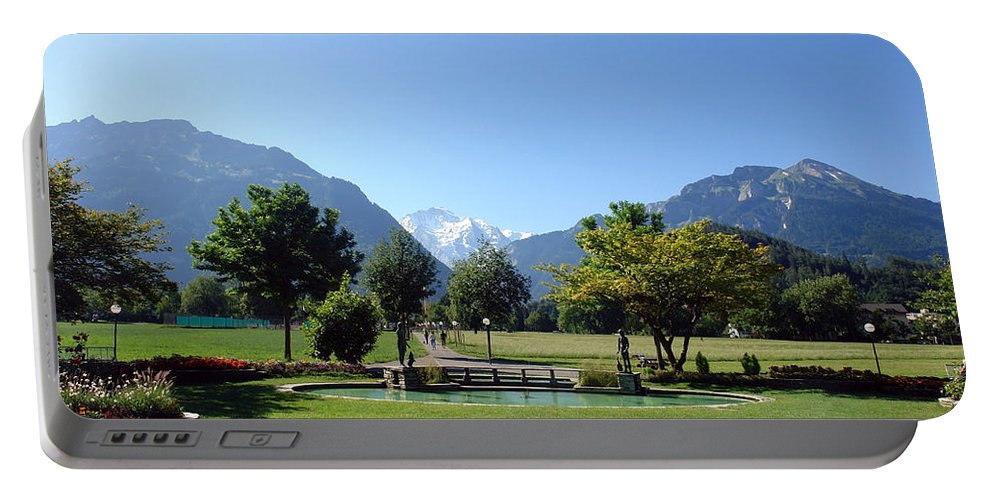 Interlaken Portable Battery Charger featuring the photograph An Open Field In Interlaken With A View Of The Mountains In The Background by Ashish Agarwal