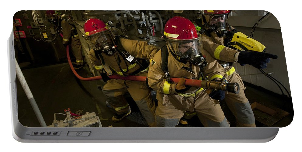 Warship Portable Battery Charger featuring the photograph Firemen Combat A Simulated Fire Aboard by Stocktrek Images