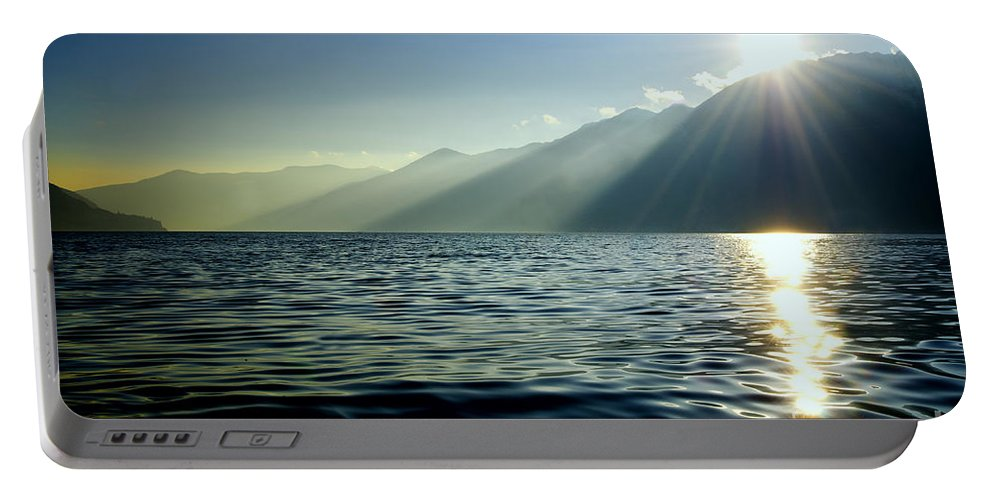 Sea Portable Battery Charger featuring the photograph Sunlight Over A Lake With Mountain by Mats Silvan