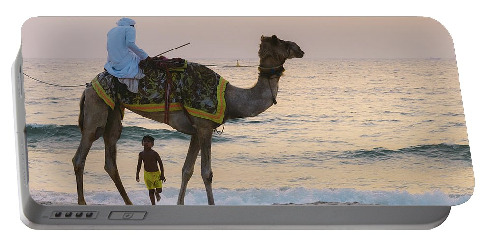 Portable Battery Charger featuring the photograph Little Boy Stares In Amazement At A Camel Riding On Marina Beach In Dubai, United Arab Emirates - by Alexandre Rotenberg