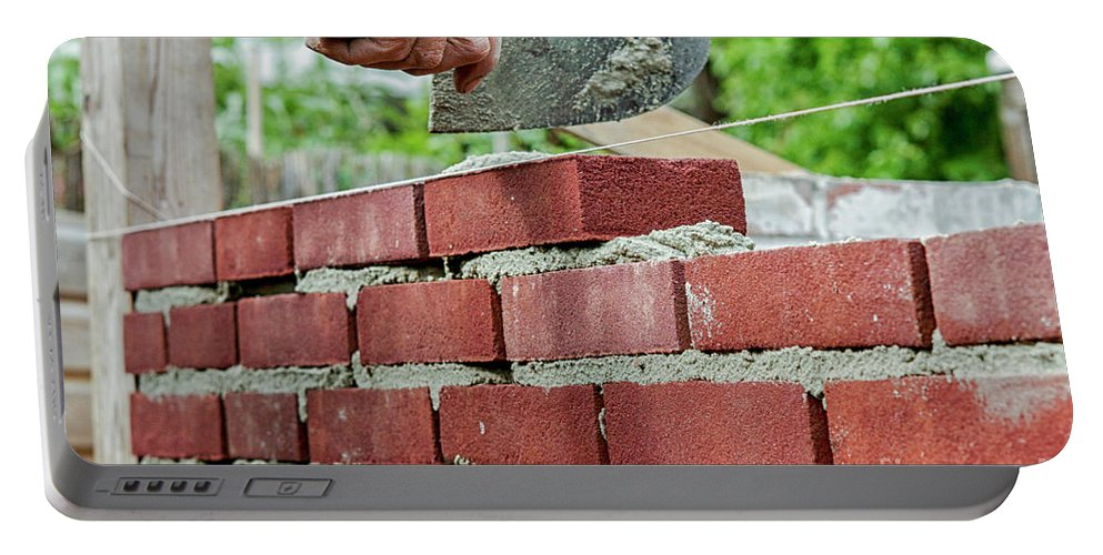 Activity Portable Battery Charger featuring the photograph Bricklaying by Patricia Hofmeester