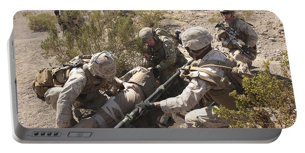 Combat Portable Battery Charger featuring the photograph A Medic Treats Injuries On A Downed by Stocktrek Images