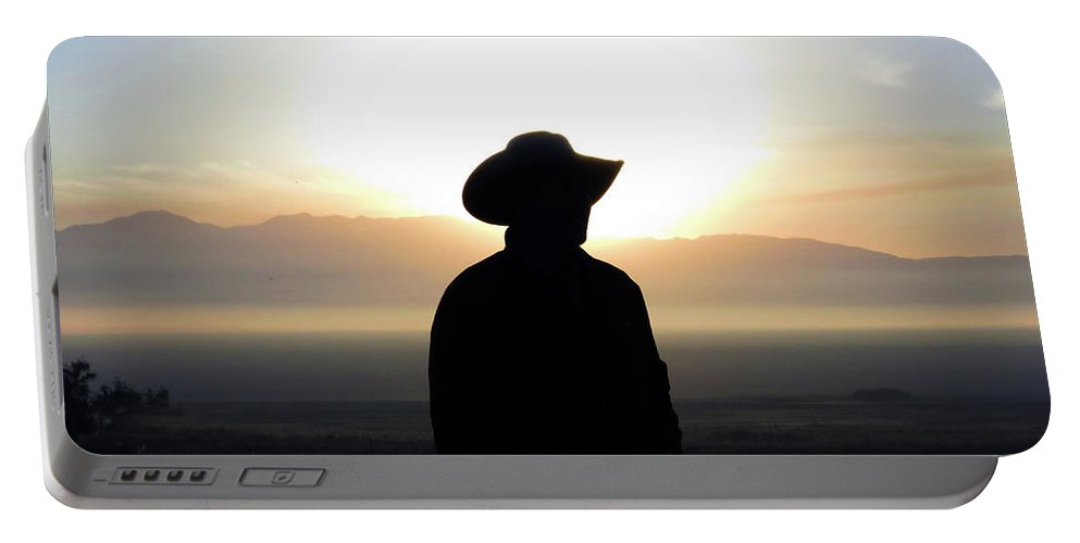 Cowboy Portable Battery Charger featuring the photograph America's Cowboy At Sunrise by Mike Fisher