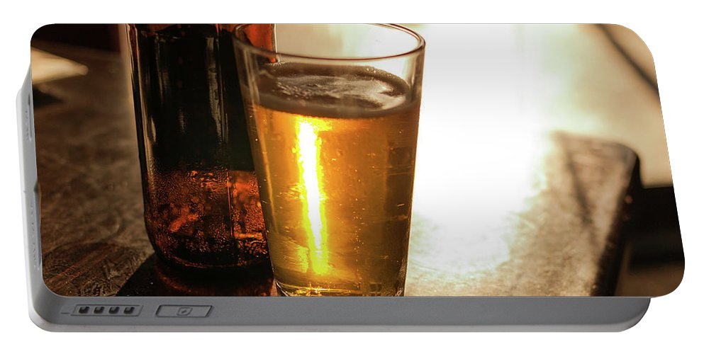Back Lit Portable Battery Charger featuring the photograph Backlit Glass Of Beer And Empty Bottle On Table by Bradley Hebdon
