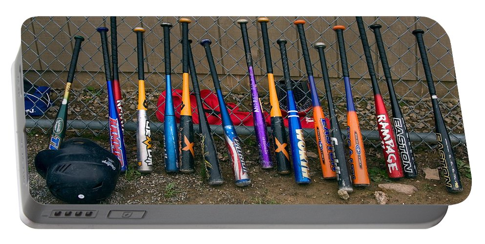 17 Kids' Baseball Bats Lined Up Along Fence Portable Battery Charger featuring the photograph Batter's Choice by Sally Weigand