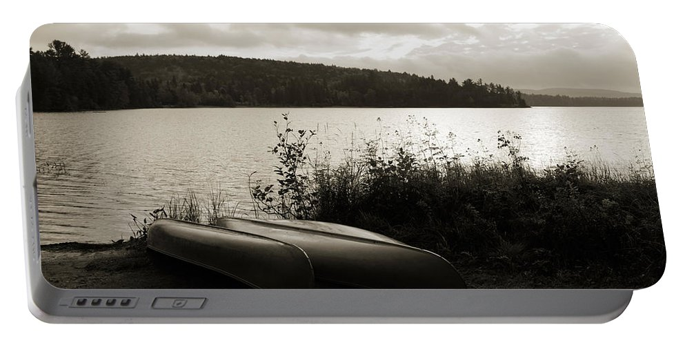 Lake Portable Battery Charger featuring the photograph Canoe On A Shore Of A Lake At Dawn by Oleksiy Maksymenko