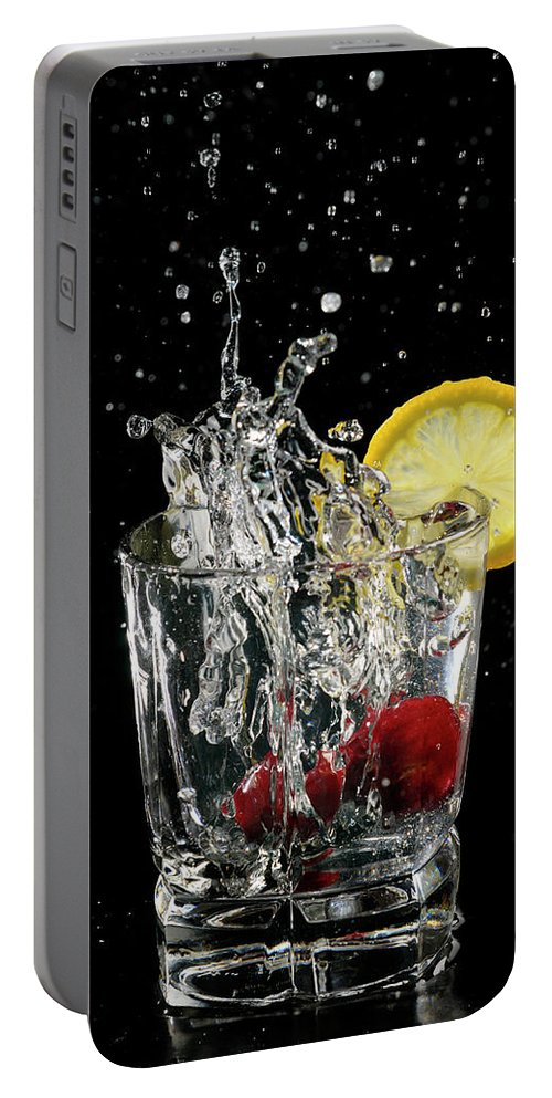 Cherries Portable Battery Charger featuring the photograph Cherries Splashing Into Sparkling Water Glass With Lemon Slice O by Reimar Gaertner