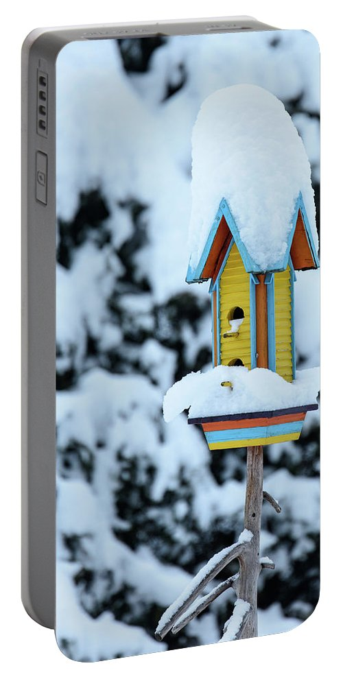 Winter Portable Battery Charger featuring the photograph Colorful Wooden Birdhouse In The Snow by Nicola Simeoni