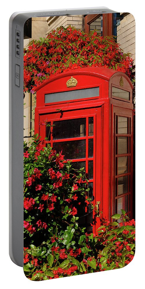 Old Portable Battery Charger featuring the photograph Old Red Telephone Box Or Booth Surrounded By Red Flowers In Toro by Reimar Gaertner