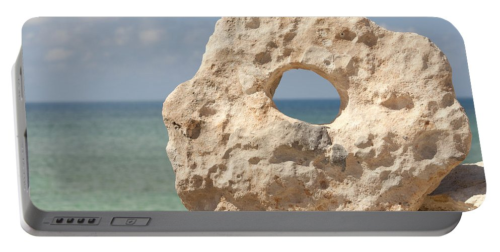 Arrangement Portable Battery Charger featuring the photograph Rock With A Hole With A Tropical Ocean In The Background. by Anthony Totah