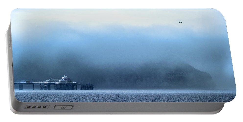 Pier Portable Battery Charger featuring the photograph The Sea Mist Lifts To Reveal The Great Orme Behind Llandudno Pier by Mal Bray