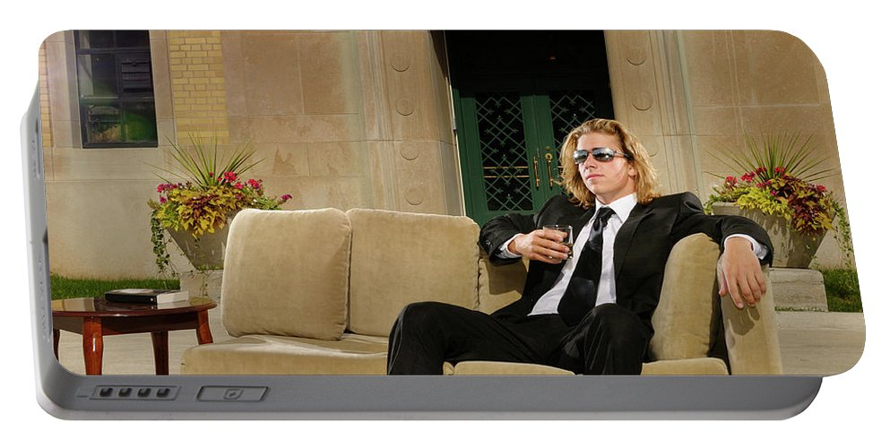 Rich Portable Battery Charger featuring the photograph Wealthy Young Man In Suit Sitting On A Couch With A Drink On A T by Reimar Gaertner