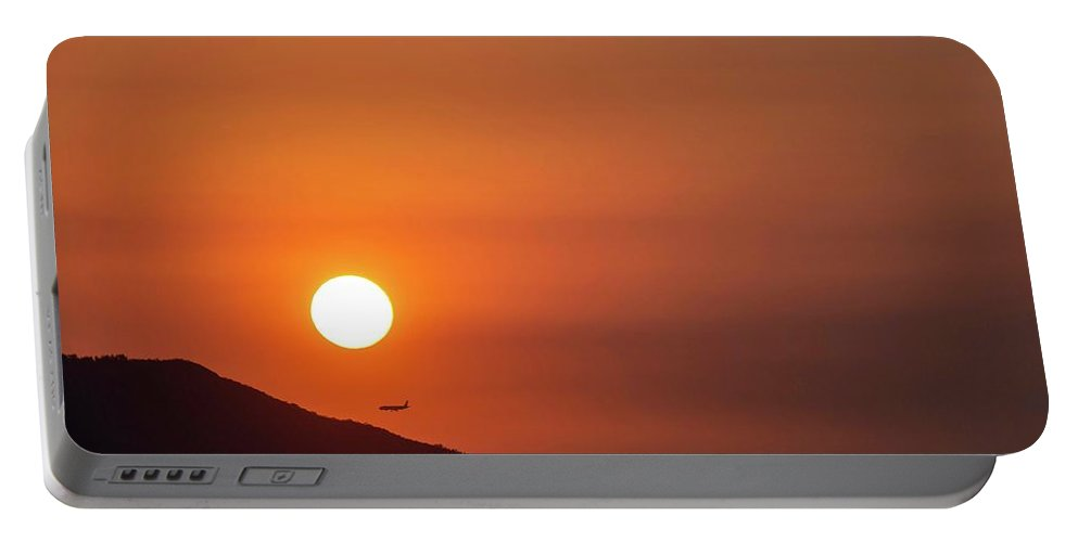 Sunset Portable Battery Charger featuring the photograph Red sunset and plane in flight by Hannes Roeckel