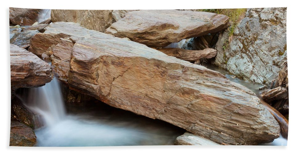 Cascade Beach Towel featuring the photograph Small Waterfall Casdcading Over Rocks In Blue Pond by Stephan Pietzko