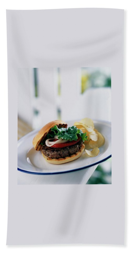 A Burger With Potato Chips Beach Towel