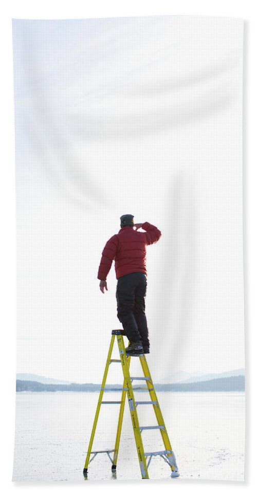 Arm Raised Beach Towel featuring the photograph Man Atop Ladder On A Frozen Lake by Woods Wheatcroft