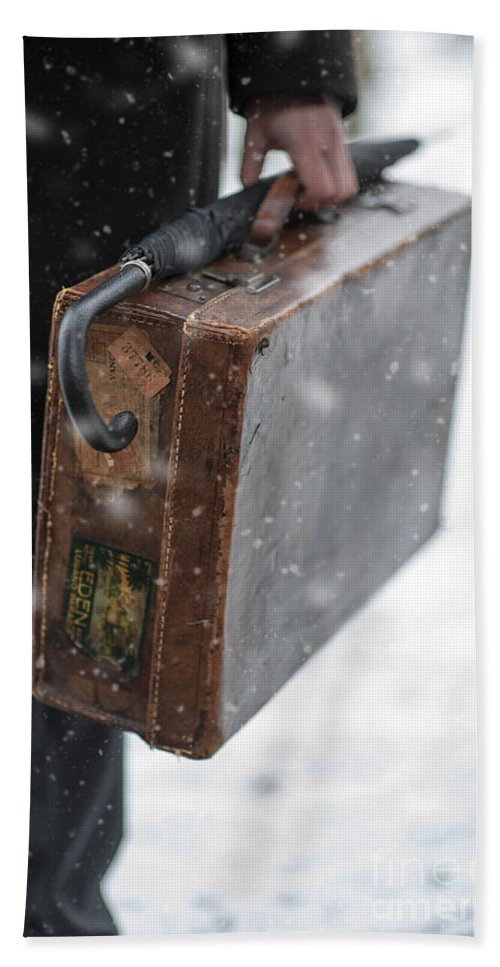 Suitcase Beach Towel featuring the photograph Man Holding A Vintage Leather Suitcase In Winter Snow by Lee Avison