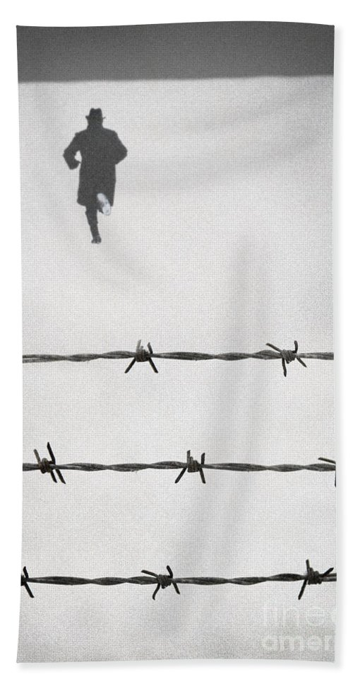 Man Beach Towel featuring the photograph Man Wearing Hat And Coat Running From Barbed Wire Fence In Snow by Lee Avison