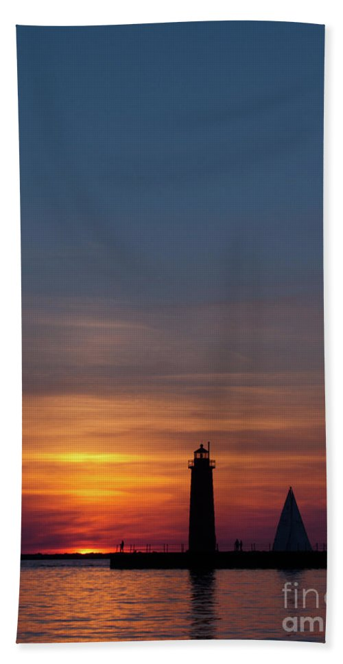 Sailboat Beach Towel featuring the photograph Muskegon Lighthouse Silhouetted At Sunset With A Sailboat In The by John Harmon