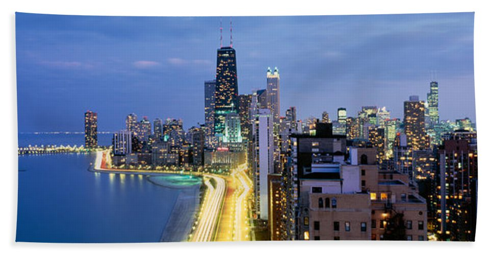 Photography Beach Towel featuring the photograph Skyscrapers Lit Up At The Waterfront by Panoramic Images