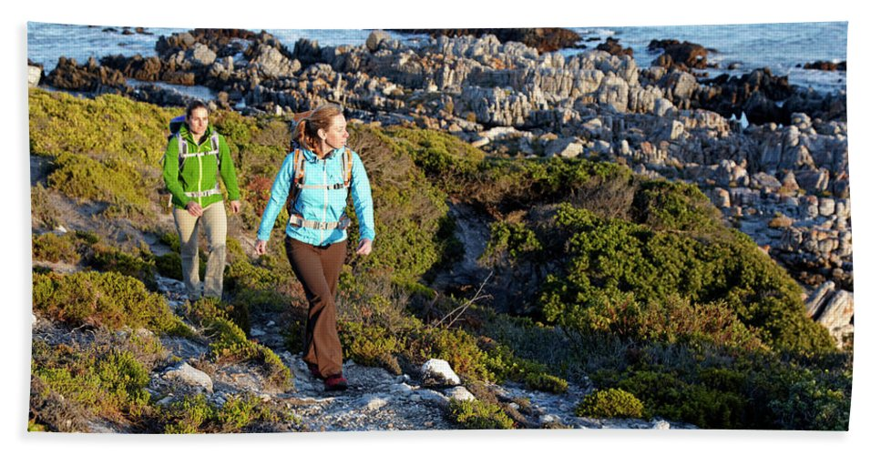 Adventure Beach Towel featuring the photograph Two Women Hiking On An Ocean Trail by Lars Schneider