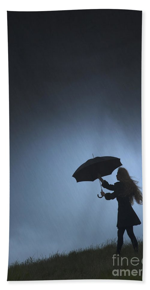 Woman Beach Towel featuring the photograph Woman Holding An Umbrella Against A Threatening Sky by Lee Avison