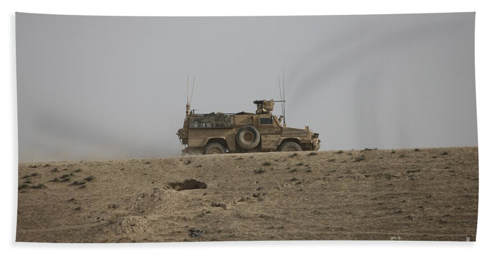 Isaf Beach Towel featuring the photograph An Mrap Vehicle Patrols The Ridge by Terry Moore